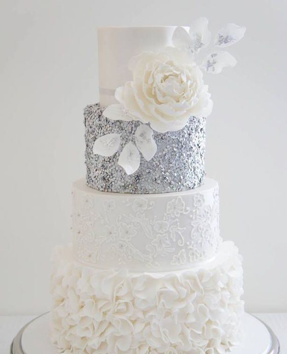 a white and silver wedding cake with textural and patterned tiers, an oversized white sugar bloom is very refined