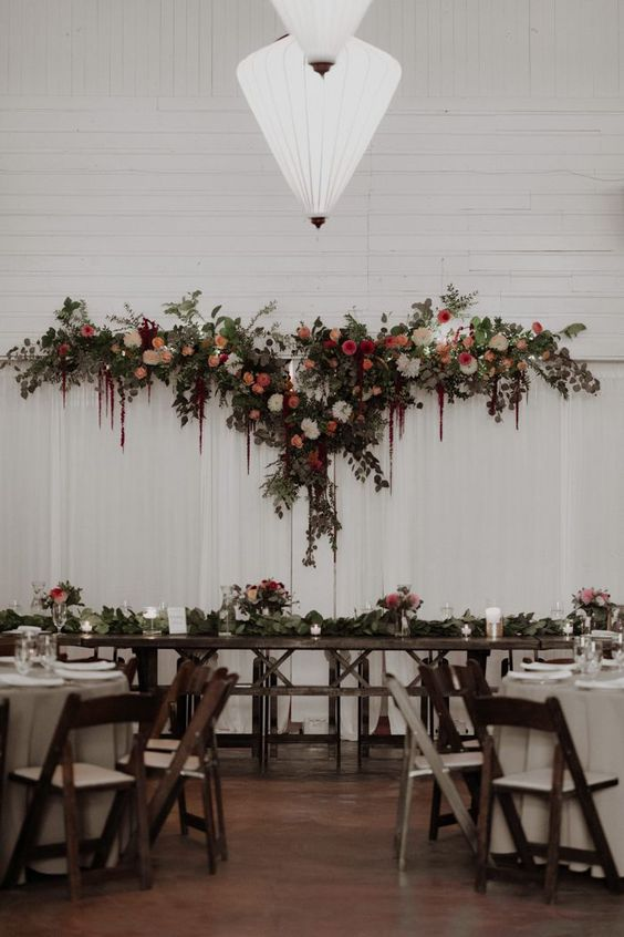 a white curtain backdrop with lush greenery and bright blooms on top plus matching florals on the tables