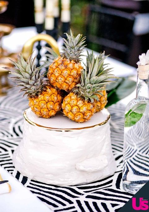 a white textural wedding cake with a gold leaf edge and mini pineapples on top is a very fresh and modern idea