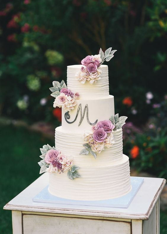 a white textural wedding cake with a monogram and neutral and purple blooms and foliage of sugar