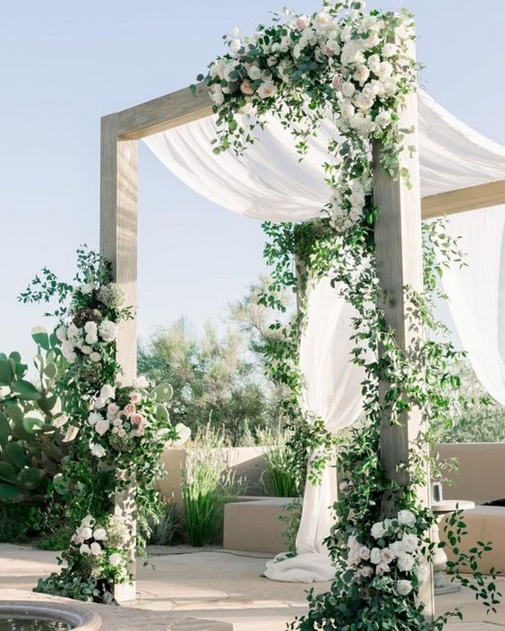 a white wedding arch with curtainsm greenery and white blooms looks luxurious