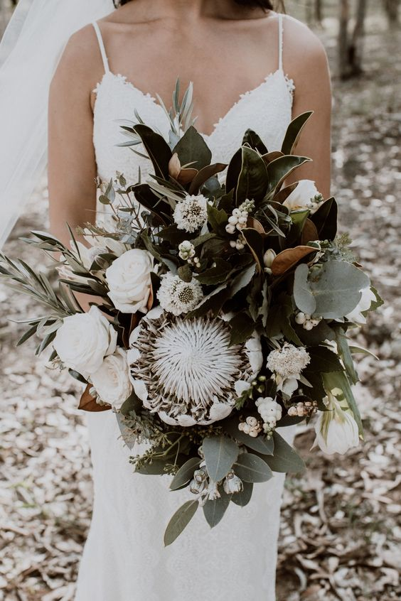a white wedding bouquet of king proteas, white roses, berries, magnolia leaves and pale greenery