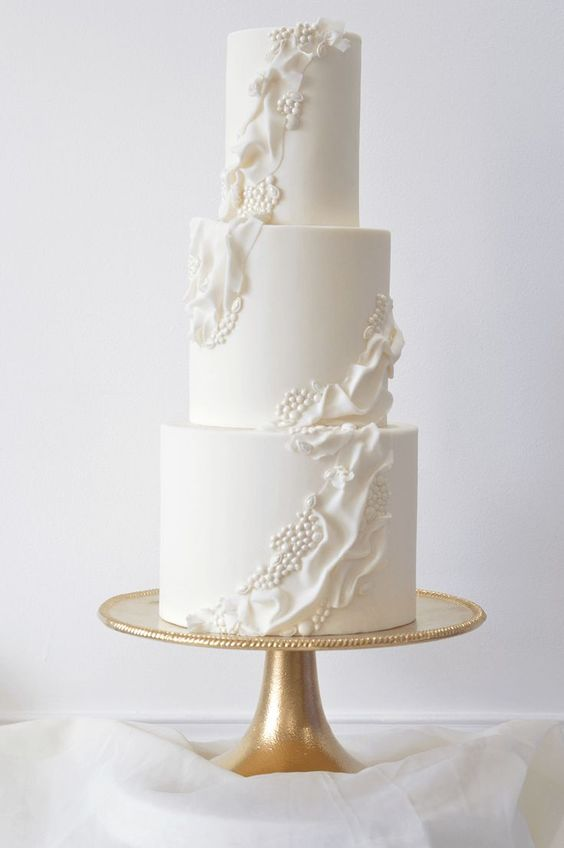 a white wedding cake with ruffles and beads is a very chic idea inspired by vintage designs
