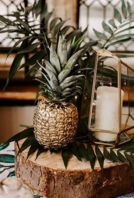 a wood slice, greenery, a candle lantern shaped as a terrarium and a gilded pineapple for a cool wedding centerpiece