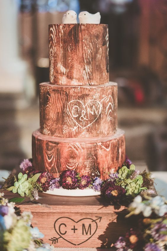 a woodland wedding cake imitating real wood, with fresh blooms, greenery and birdie toppers is super cute