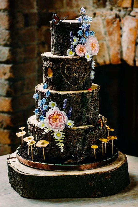 a woodland wedding cake imitating wood cuts, with fresh blooms and fake mushrooms looks very real