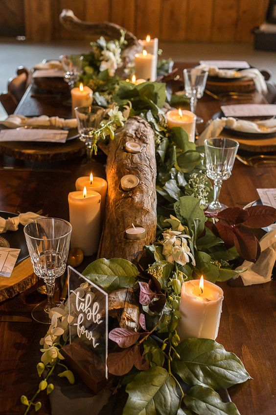 a woodland wedding centerpiece of a tree branch, leaves and foliage, candles and an acrylic sign