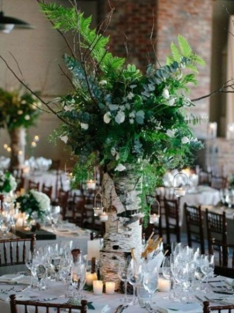 a woodland wedding centerpiece of a tree stump, white blooms, greenery and candle holders hanging on branches