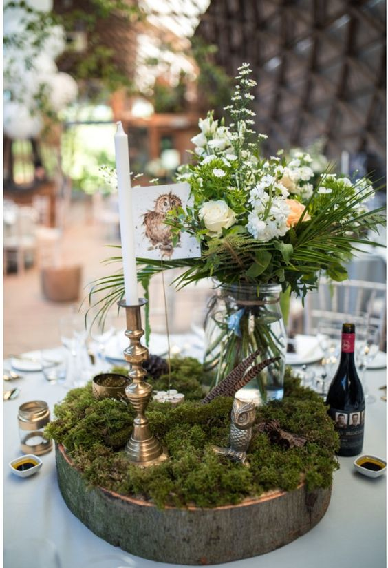 a woodland wedding centerpiece of a wood slice, moss, blooms and greenery in a jar, feathers and candles