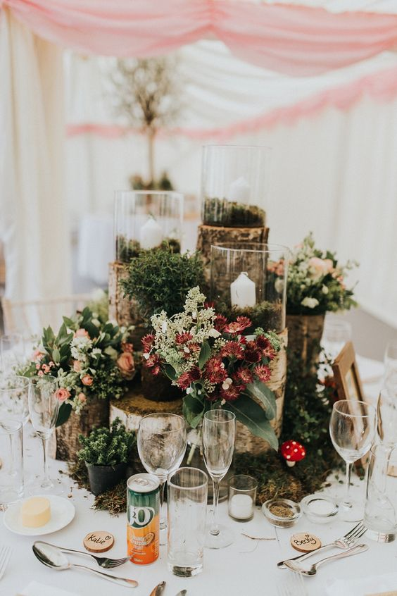 a woodland wedding centerpiece of tree stumps, moss, succulents, greenery, blooms and candles and little mushrooms