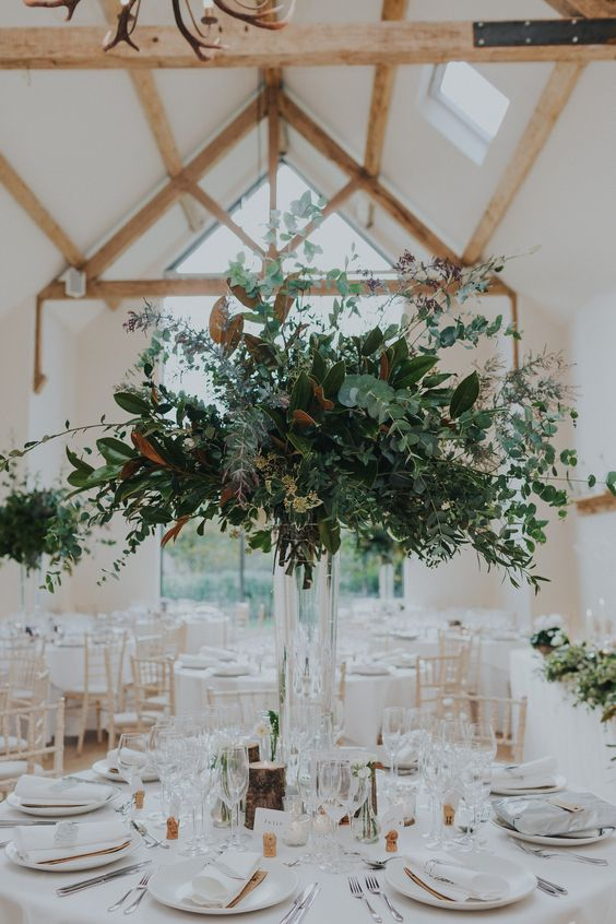a woodland wedding centerpiece with a tall clear vase and lots of textural greenery and foliage