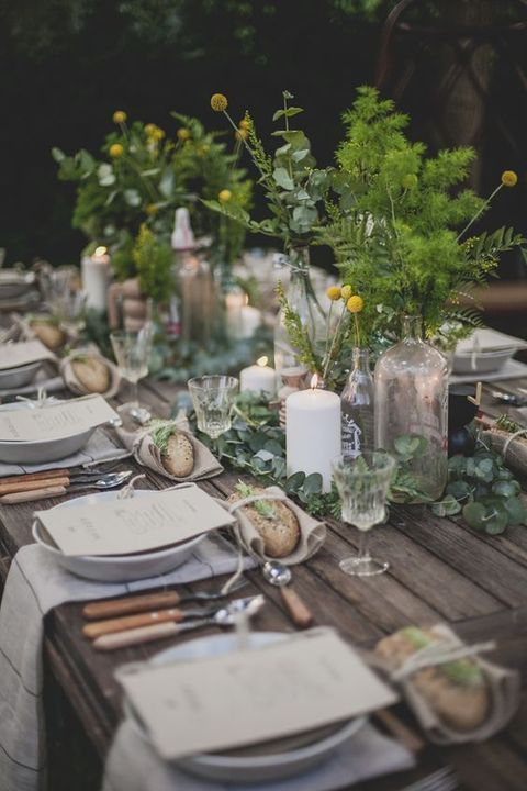 a woodland wedding tablescape with fresh eucalyptus, greenery and billy balls in clear vases plus candles