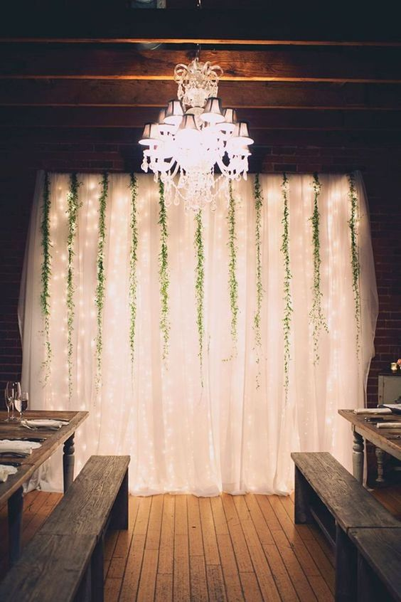 airy curtains with greenery hanging down and lights is a cool and bright idea that creates an ambience