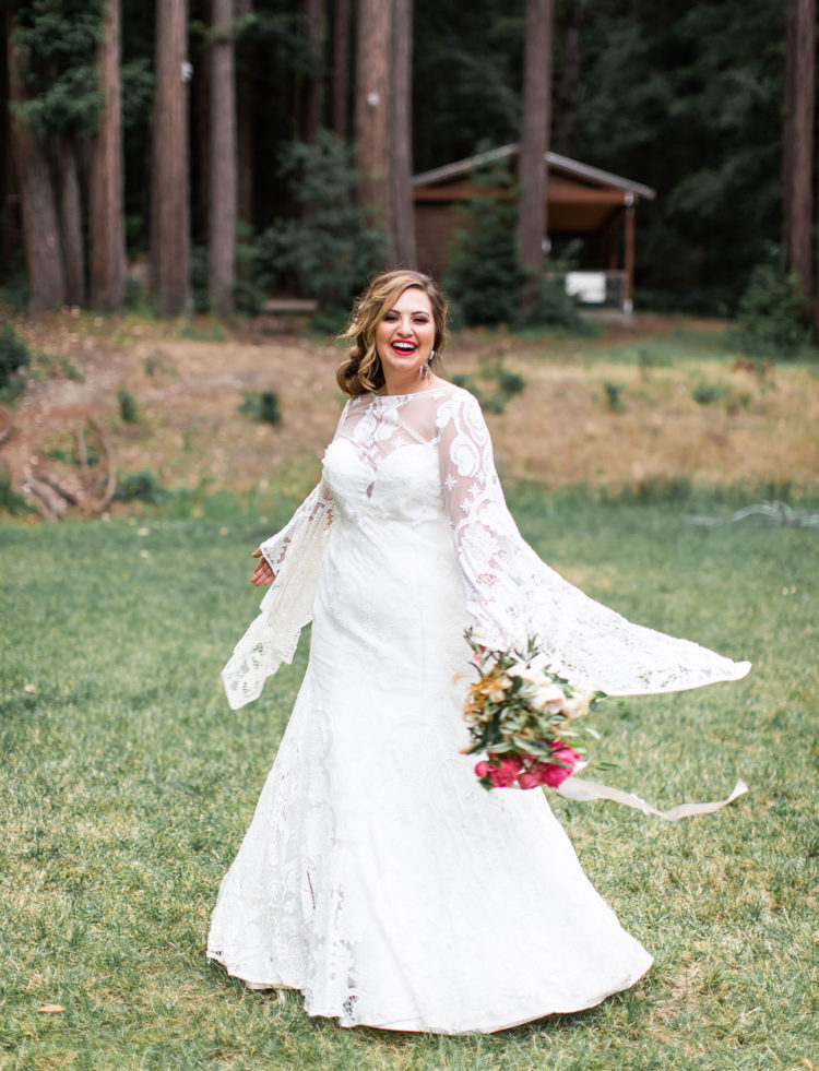 an A-line wedding dress with extra long bell sleeves and a cutout back, a high illusion neckline for a summer boho bride
