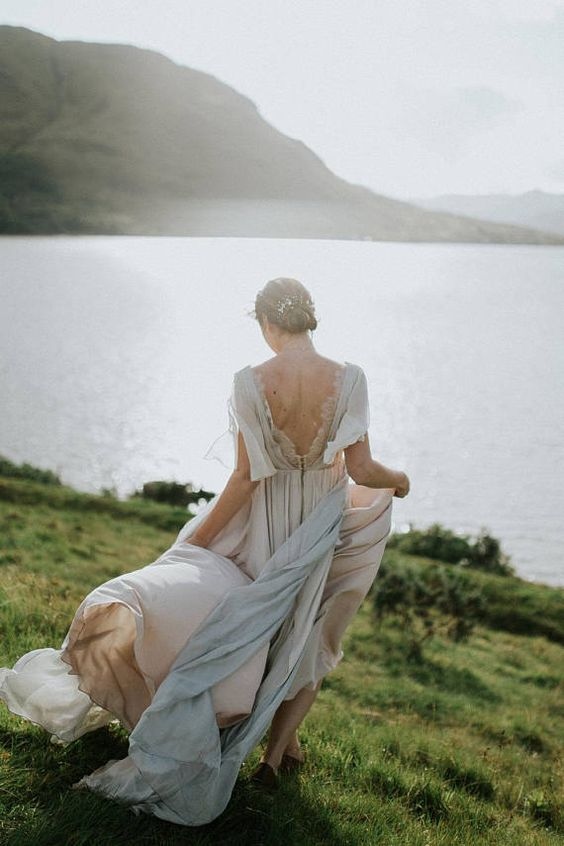 an airy and flowy grey wedding dress with short sleeves, a low back accented with lace and a pleated flowy skirt with a trian