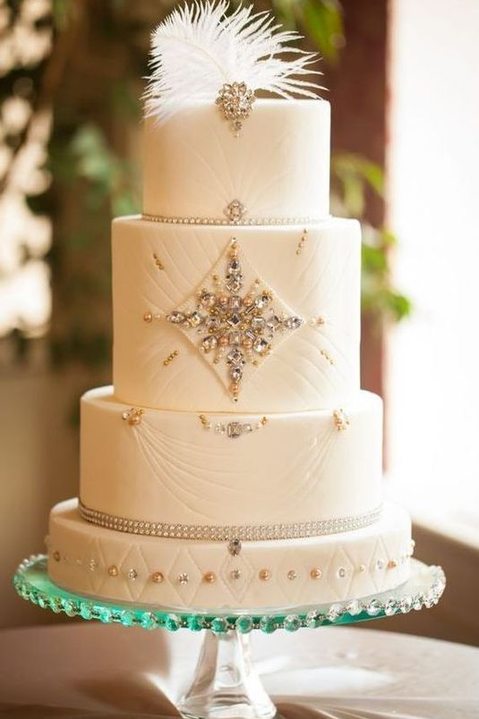 an art deco wedding cake with beautiful embellishments and a feather on top is a gorgeous sparkling idea