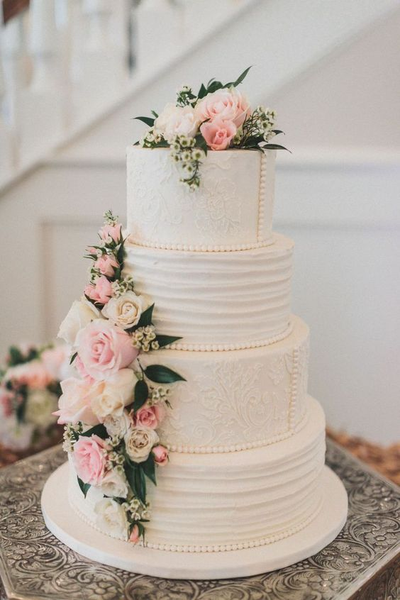 an elegant vintage wedding cake with textural tiiers and pink and white blooms plus greenery and beads of sugar