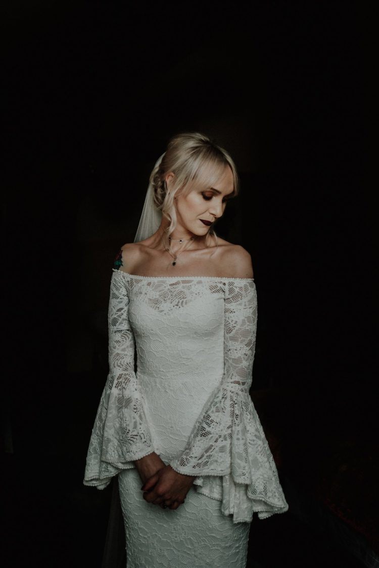 an off the shoulder lace sheath wedding dress with bell sleeves and a dark lipstick for a moody gothic wedding
