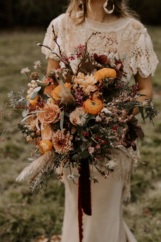 an oversized boho wedding bouquet of marigold, burgundy blooms, lots of berries, greenery and twigs