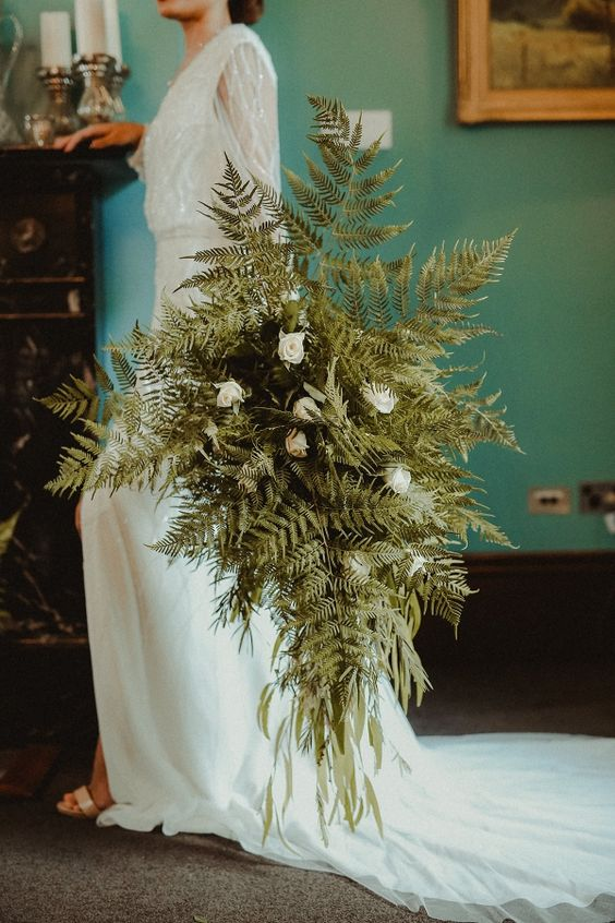 an oversized fern and white rose wedding bouquet with plenty of texture and dimension is a pretty idea for a woodland wedding