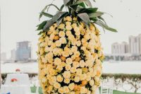an oversized pineapple composed of peachy blooms and foliage marks the wedding escort cards and mini pineapples add to the decor