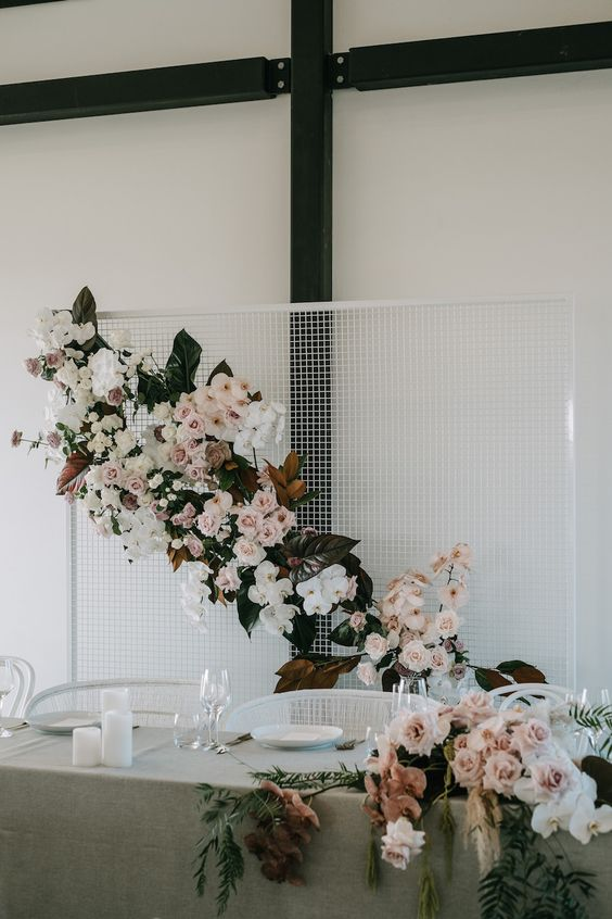 an ultra-modern white mesh backdrop with blush and white blooms, dark foliage and magnolia leaves