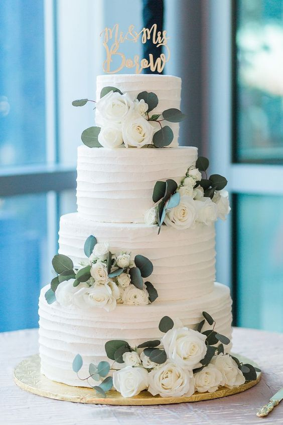 awhite textural buttercream wedding cake decorated with white blooms and greenery and with a calligraphy topper