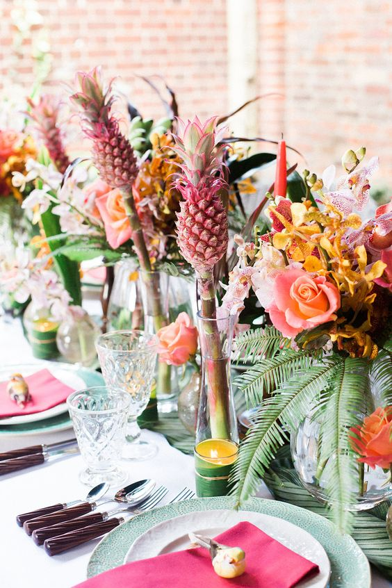 colorful tropical wedding table decor with bold blooms, greenery and pink pineapples, fuchsia napkins and green chargers