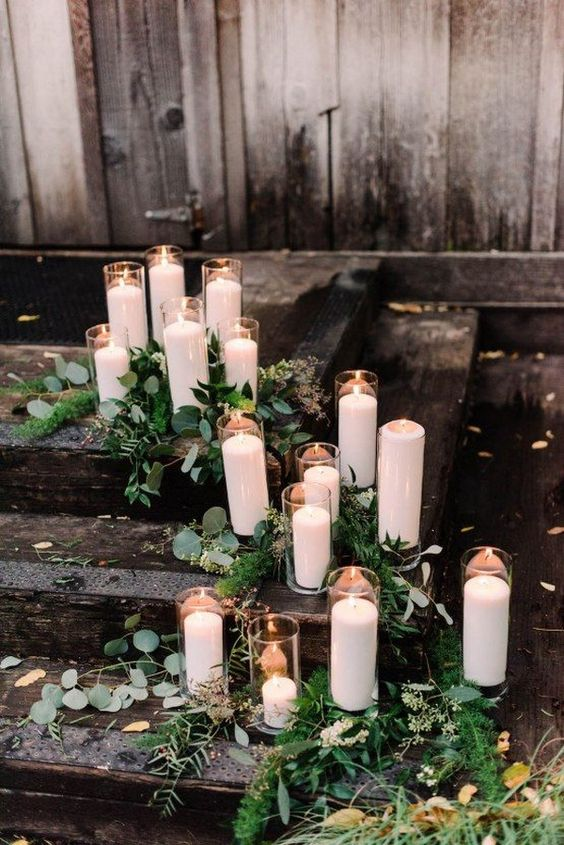 decorate your wedding space with pillar candles in white and greenery for a chic look