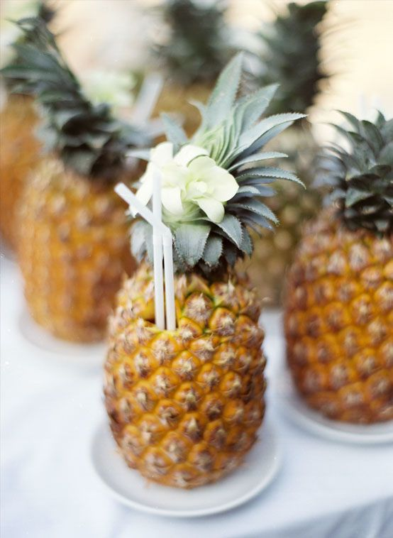 drinkable pineapples with straws are a lovely refreshing idea for a tropical wedding