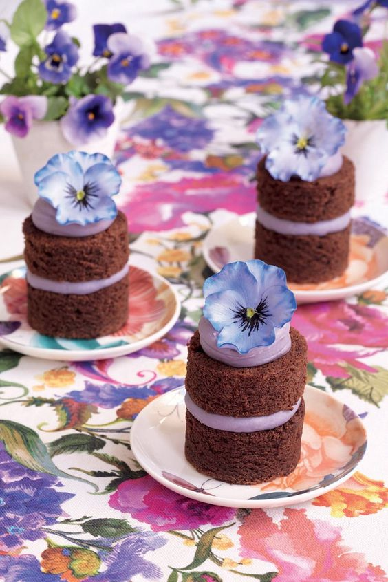 individual naked chocolate wedding cakes with blueberry cream and blooms on top