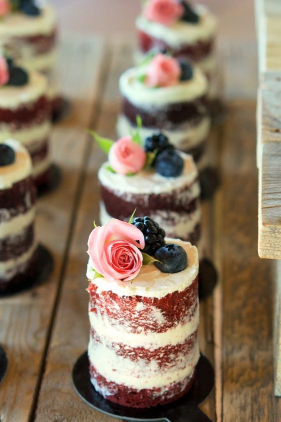 individual naked wedding cakes with a bit of buttercream on top, blueberries, blackberries and roses