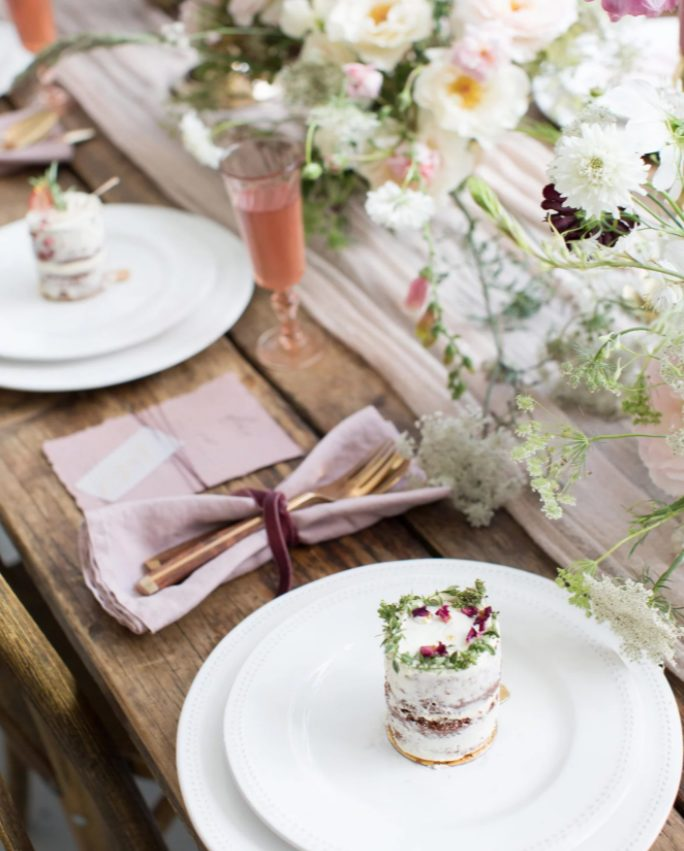 individual naked wedding cakes with chocolate, greenery and petals for a lovely spring wedding