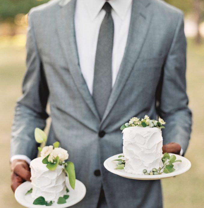 individual white buttercream cakes topped with leaves and fresh blooms are elegant classics to enjoy
