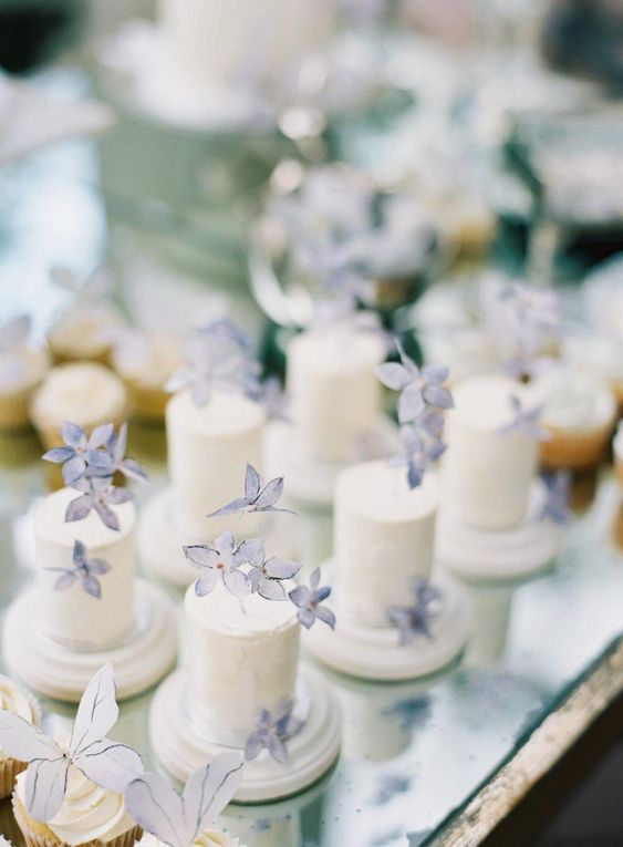 individual white buttercream wedding cakes topped with blue sugar blooms for a spring or summer wedding