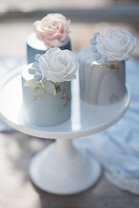 pastel blue individual wedding cakes topped with sugar berries, leaves and roses look very refined and chic