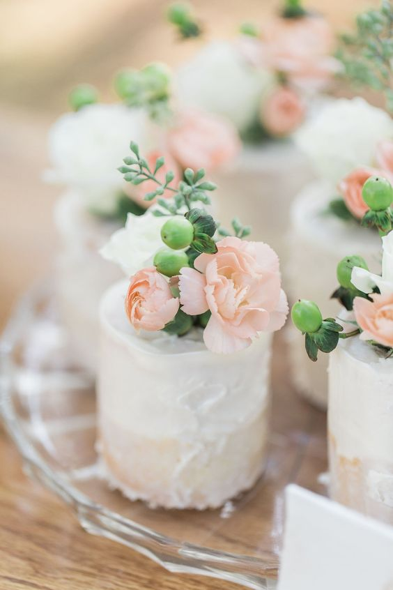 textural buttercream individual wedding cakes topped with berries and white and blush blooms