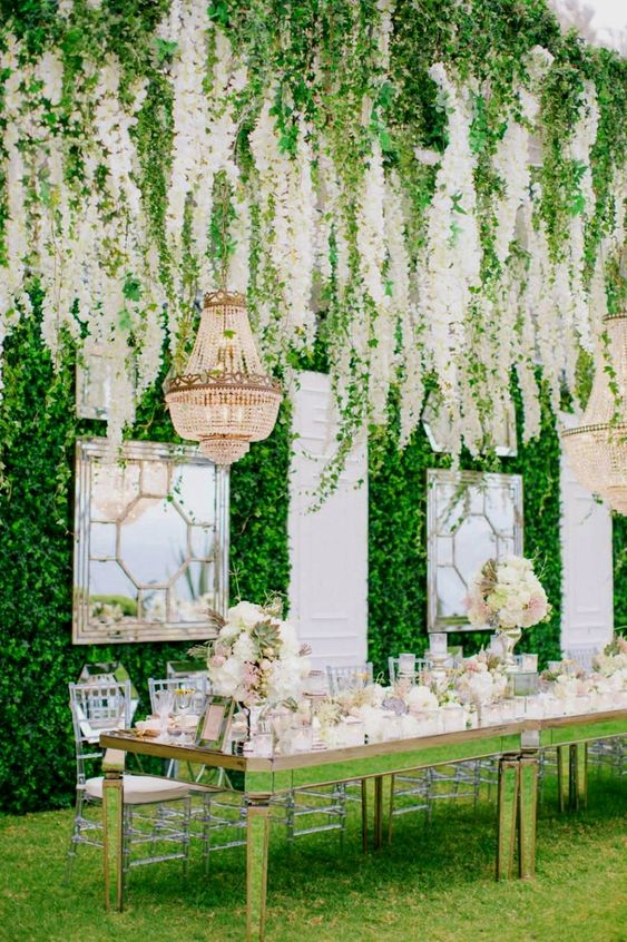 vintage mirrors with frames and a greenery wall plus a huge white bloom hanging over the reception are a refined idea