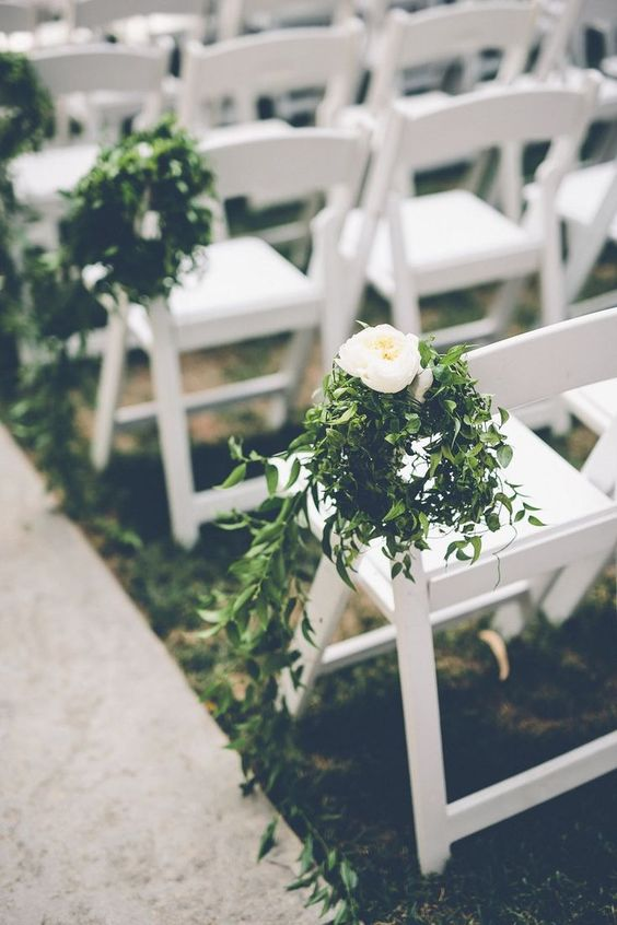 wedding aisle chairs decorated with greenery and white blooms are a chic idea