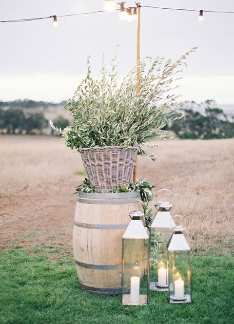 a barrel with a basket with olive branches, candle lanterns is a nice decoration for a wedding ceremony space