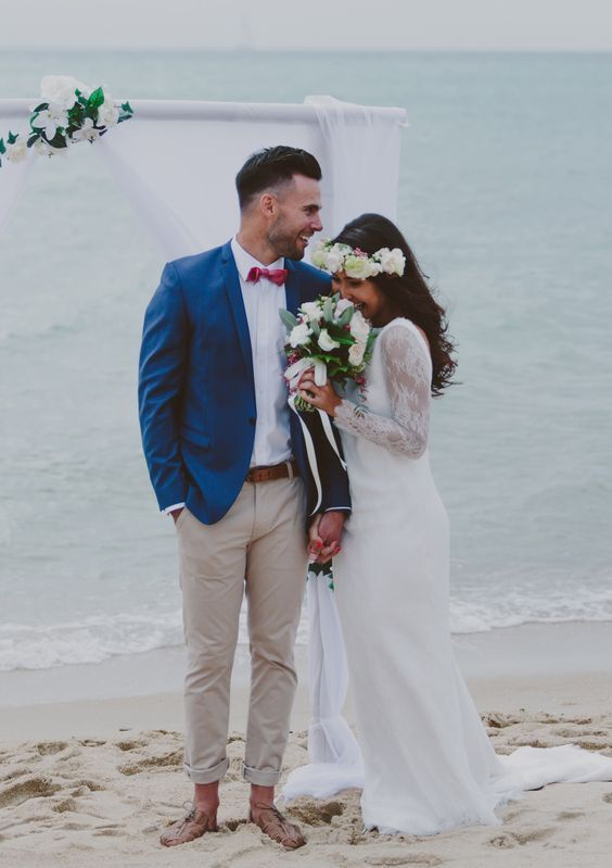 a beach groom wearing a bold blue blazer paired with a pink bow tie for a bold look
