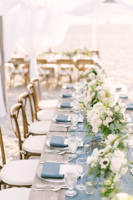 a beach wedding reception table done with a blue runner and napkins, with neutral blooms and greenery and simple cutlery