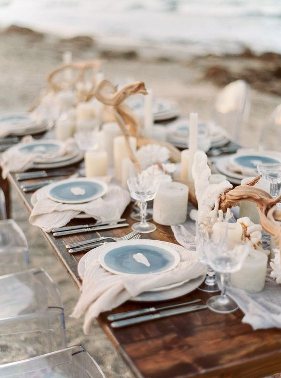 a beach wedding table with neutral and blue plates, driftwood, candles and corals looks odern and very fresh