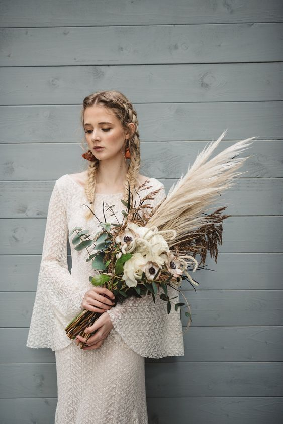 a beautiful boho woodland bridal look with a boho lace dress with bell sleeves, a high neckline, tassel earrings and braids and a lovely bouquet of pampas grass, neutral blooms and foliage