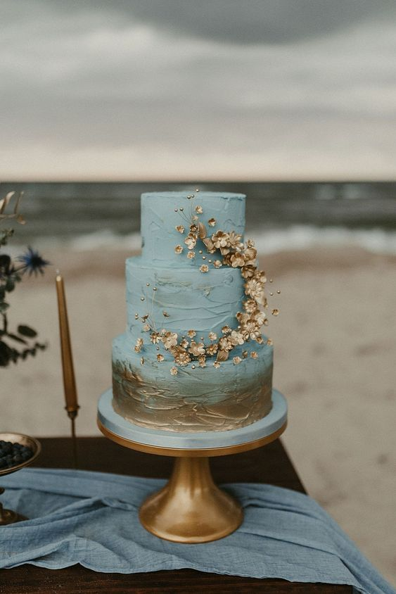 a blue and gold textural wedding cake with gold touches and gold blooms plus beads for decor