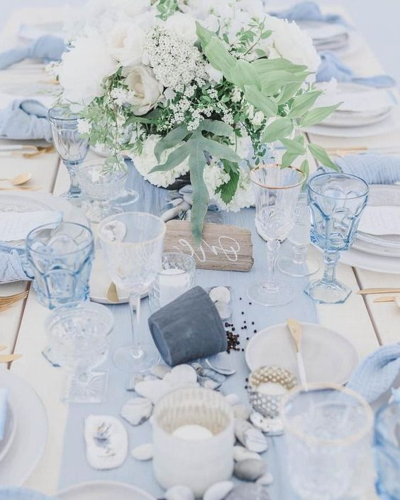 a blue beach wedding table with a light blue runner, glasses, napkins, neutral blooms, pebbles and seashells