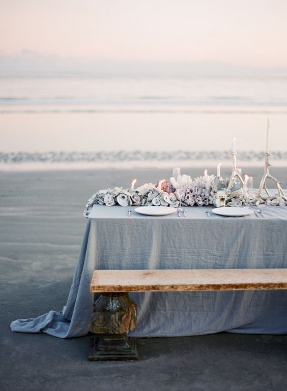 a blue beach wedding tablescape with a blue tablecloth, seashells, corals and white candles looks like it's out of the sea