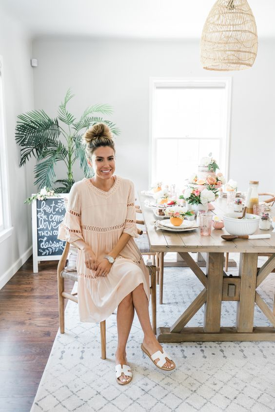 a blush boho midi dress with lace inserts, long sleeves and elegant white sandals for a boho bridal shower at home