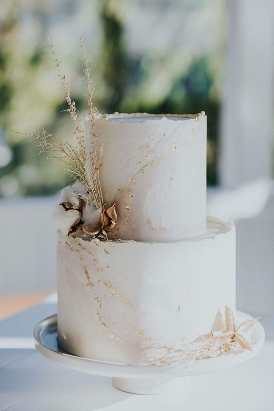 a blush marble textural wedding cake with gold leaf, dried blooms and herbs is a very refined idea