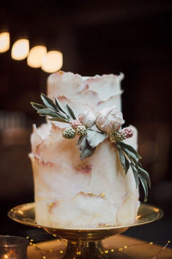 a blush textural wedding cake with gold leaf, fresh blooms and leaves is a beautiful and exquisite idea
